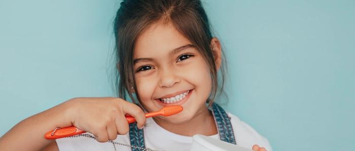 smiling young girl brushing teeth