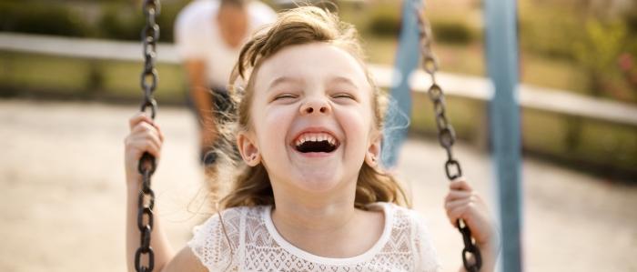 little girl smiling on swing